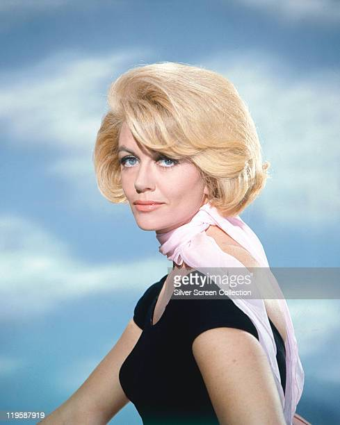 Dorothy Malone US actress wearing a black cap sleeve top with a pink scarf in a studio portrait against a background of blue sky with clouds circa...
