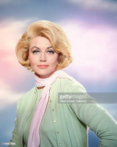 Dorothy Malone US actress wearing a pale green cardigan and top with a pink scarf in a studio portrait against a background of blue sky with clouds...