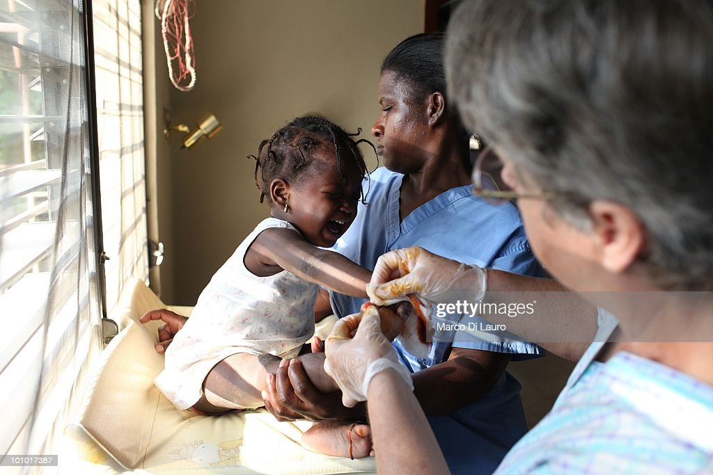 Dorothy Pearce who has not received any medical training, cuts dead flesh from an open wound on an injured child's foot as she screams in agony at the Faith Hope Love Infant Rescue Orphanage managed by a US citizen named Dorothy Pearce on February 4, 2010 in Port Au Prince, Haiti. Dorothy Pearce a US Citizen founded the Faith Hope Love Infant Rescue five years ago answering what she describes as a 'call by God' to leave her job as a real estate agent in Miami to come to Haiti. She runs the organization from her home in Port-au-Prince taking in children whose families are unable to support them. She is currently caring for 20 children. In the backyard strewn with rubbish, ten babies lie sleeping on the dirty concrete floor under a canopy of plastic sheeting, many are newborn. The older children play largely unobserved by the nannies barefoot amongst rusted tins and dirty nappies. A fetid swimming pool is covered with a cloud of mosquitoes. Three dogs, whose feces litter the small concrete play area, lick the children's faces as they play and lie on the floor. Several of the children are HIV positive and many suffer with severe disabilities. Most of the children appear listless, either clamouring to be held or curled up sleeping awkwardly on the floor. Others sit crying, unattended. One of the children, Alexandra, 2, was injured in the earthquake. Pearce who has not received any medical training, cuts dead flesh from an open wound on the injured child's foot as she screams in agony. Pearce has not registered her charity with the Haitian government and the orphanage is entirely unregulated. Prior to the earthquake that devastated the island on January 12th, there were an estimated 380,000 children living in orphanages in Haiti, 500 of which were unregistered.