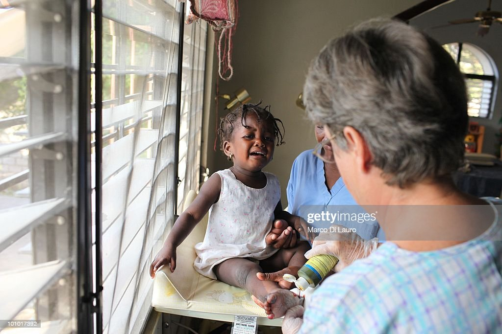 Dorothy Pearce who has not received any medical training, cuts dead flesh from an open wound on an injured child's foot as she screams in agony at the Faith Hope Love Infant Rescue Orphanage managed by a US citizen named Dorothy Pearce on February 4, 2010 in Port Au Prince, Haiti. Dorothy Pearce a US Citizen founded the Faith Hope Love Infant Rescue five years ago answering what she describes as a 'call by God' to leave her job as a real estate agent in Miami to come to Haiti. She runs the organization from her home in Port-au-Prince taking in children whose families are unable to support them. She is currently caring for 20 children. In the backyard strewn with rubbish, ten babies lie sleeping on the dirty concrete floor under a canopy of plastic sheeting, many are newborn. The older children play largely unobserved by the nannies barefoot amongst rusted tins and dirty nappies. A fetid swimming pool is covered with a cloud of mosquitoes. Three dogs, whose feces litter the small concrete play area, lick the children's faces as they play and lie on the floor. Several of the children are HIV positive and many suffer with severe disabilities. Most of the children appear listless, either clamouring to be held or curled up sleeping awkwardly on the floor. Others sit crying, unattended. One of the children, Alexandra, 2, was injured in the earthquake. Pearce who has not received any medical training, cuts dead flesh from an open wound on the injured child's foot as she screams in agony. Pearce has not registered her charity with the Haitian government and the orphanage is entirely unregulated. Prior to the earthquake that devastated the island on January 12th, there were an estimated 380,000 children living in orphanages in Haiti, 500 of which were unregistered. Since the disaster, in which thousands of children were separated from their families, the dangers facing Haiti's orphans have never been more acute. (Photo by Marco Di Lauro/G