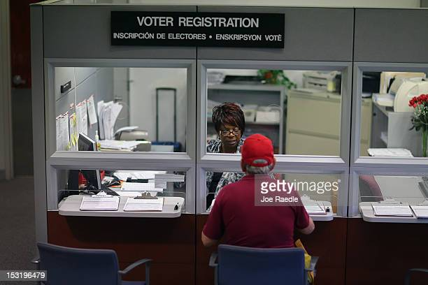 Dorothy Torrence from the MiamiDade Elections Department helps a voter fill out his registration form on October 1 2012 in Miami Florida With the...