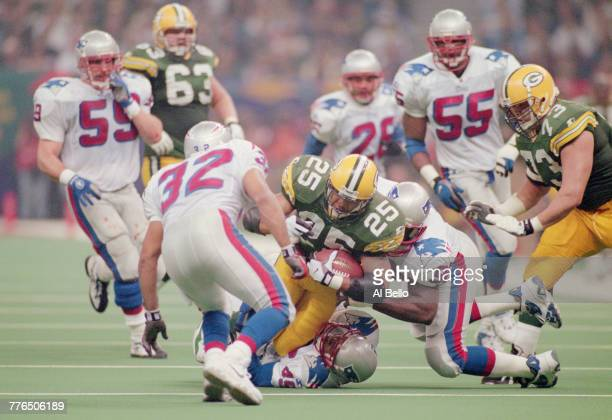 Dorsey Levens Running Back for the Green Bay Packers running the ball is tackled by Defensive Back Otis Smith and Mike Jones of the New England...