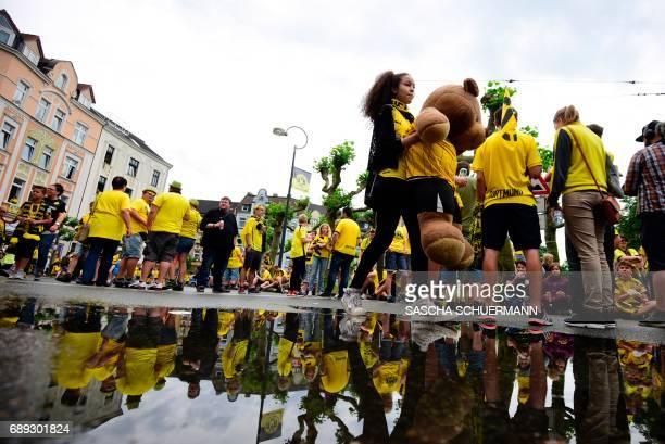 A Dortmund fan holds a teddy bear dressed in the Dortmund jersey ahead celebrations of Bundesliga soccer club Borussia Dortmund after winning the...