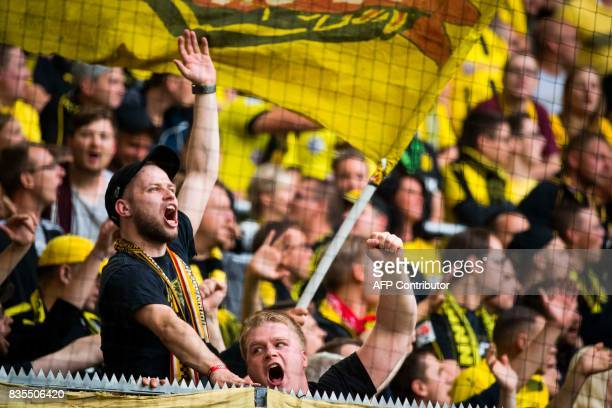 Dortmund fans cheer their team during the German First division Bundesliga football match VfL Wolfsburg v BVB Borussia Dortmund in Wolfsburg western...
