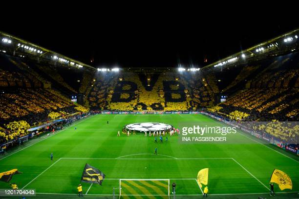 Dortmund fans display their team's logo as the teams walk in prior to the UEFA Champions League Last 16 firstleg football match BVB Borussia Dortmund...