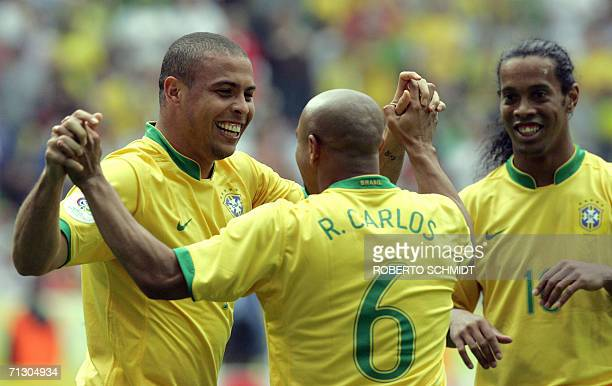 Brazilian defender Roberto Carlos congratulates Brazilian forward Ronaldo as Brazilian midfielder Ronaldinho joins them to celebrate after Ronaldo...
