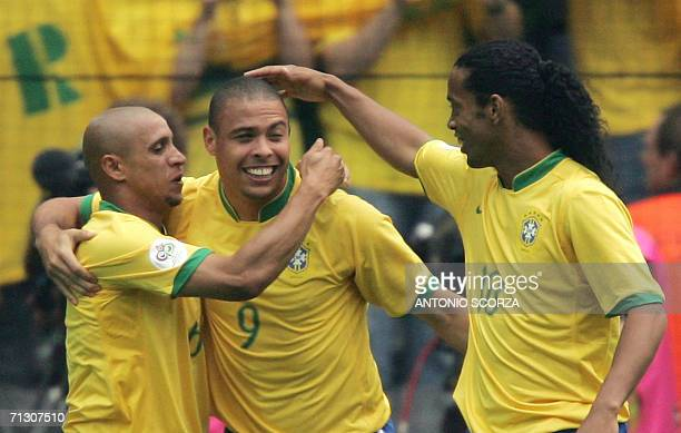 Brazilian forward Ronaldo celebrates with Brazilian defender Roberto Carlos and Brazilian midfielder Ronaldinho after scoring his team's first goal...