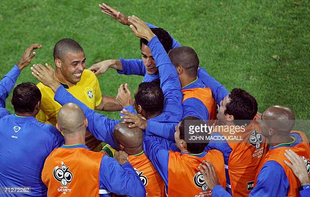 Brazilian substitutes congratulate forward Ronaldo after he scored and egalized during the opening round Group F World Cup football match Japan vs...