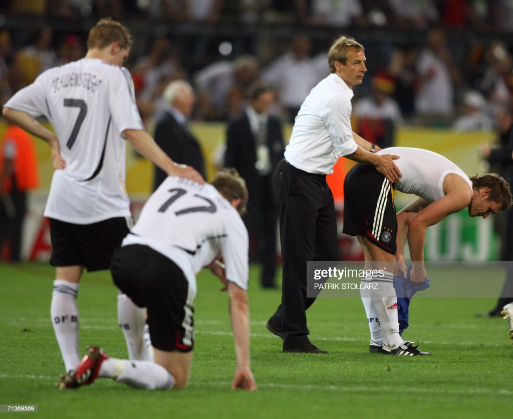 German head coach Juergen Klinsmann (2ndR) comforts German forward Oliver Neuville (R) next to German midfielder Bastian Schweinsteiger (L) and German defender Per Mertesacker at the end of the World Cup 2006 semi final football game Germany vs. Italy, 04 July 2006 at Dortmund stadium. Italy won 2 to 0 after extra-time.