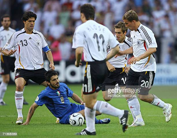 Italian midfielder Gennaro Gattuso lies on the field surrounded by German midfielder Michael Ballack Miroslav Klose Philipp Lahm and Lukas Podolski...