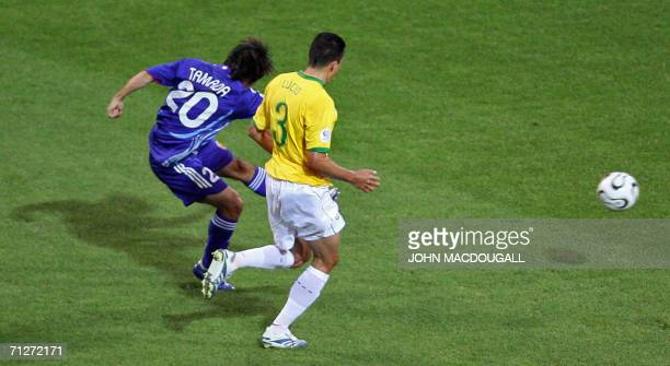 Japanese forward Keiji Tamada shoots and scores in despite of Brazilian defender Lucio's opposition during the opening round Group F World Cup...