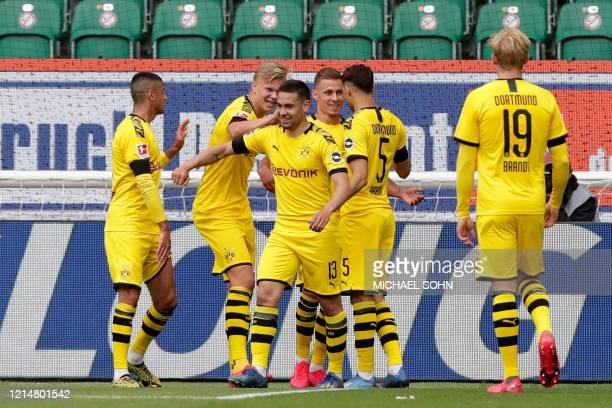 Dortmund players celebrate after Dortmund's Portuguese defender Raphael Guerreiro scored the opening goal during the German first division Bundesliga...