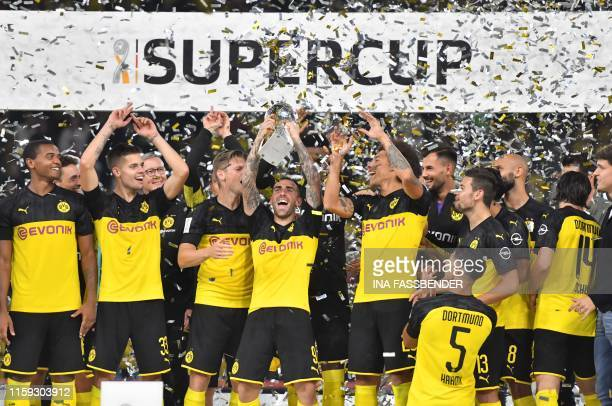 Dortmund players celebrate with the trophy after the German Supercup football match BVB Borussia Dortmund v FC Bayern Munich on August 3, 2019 at the...