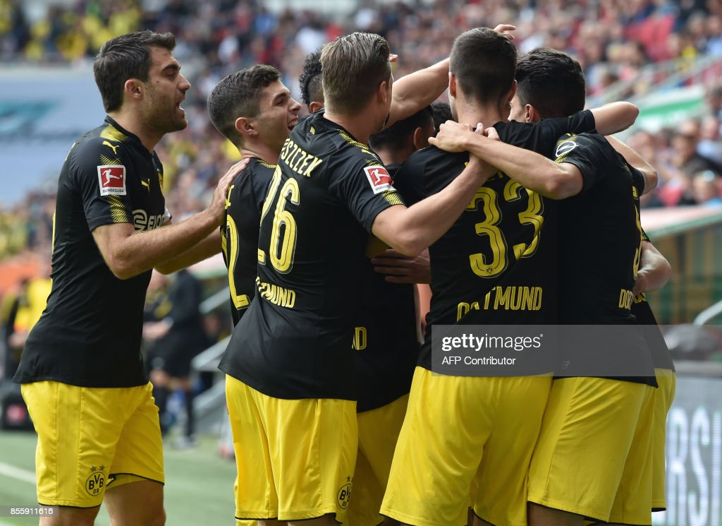 Dortmund players celebrates scoring the opening goal during the German first division Bundesliga football match between FC Augsburg and Borussia Dortmund in Augsburg, southern Germany on September 30, 2017. / AFP PHOTO / Christof