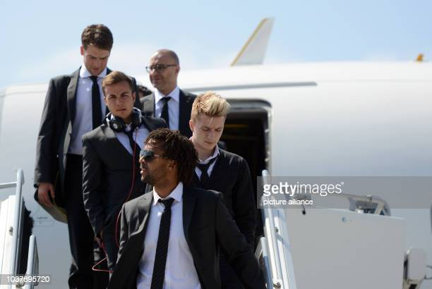 Dortmund players Mario Götze , Marco Reus and Patrick Owomoyela exit the plane after their arrival from Madrid at the airport in Dortmund, Germany,...
