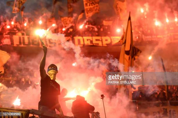 Dortmund supporters burn fireworks during the German first division Bundesliga football match Fortuna Duesseldorf v Borussia Dortmund in Duesseldorf...