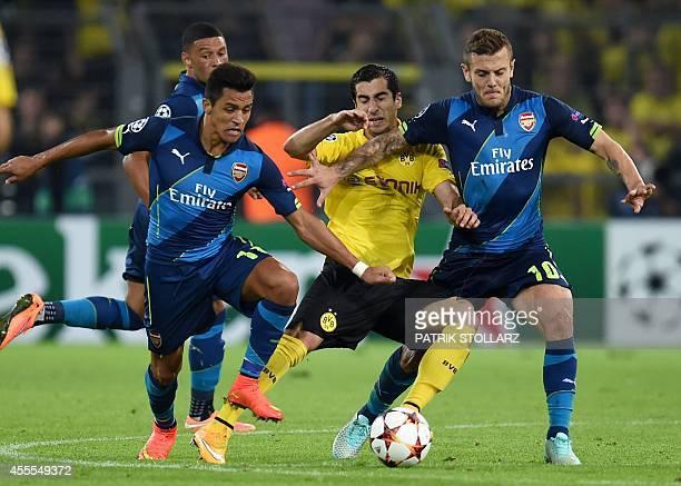 Dortmund's Armenian midfielder Henrikh Mkhitaryan is pressured by Arsenal's English midfielder Jack Wilshere and Arsenal's Chilean striker Alexis...