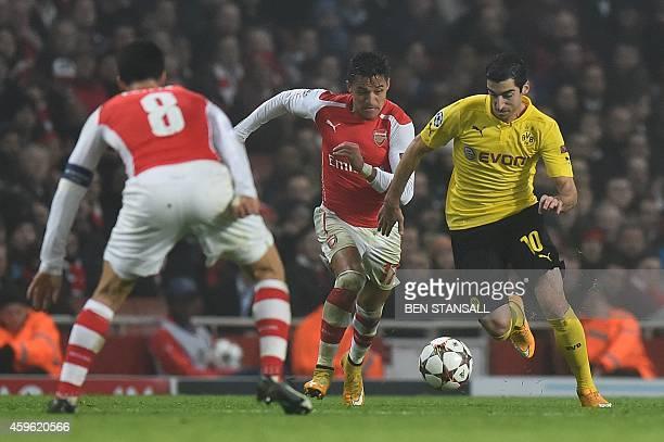 Dortmund's Armenian midfielder Henrikh Mkhitaryan vies with Arsenal's Chilean striker Alexis Sanchez during the UEFA Champions League Group D...