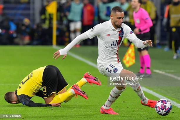 Dortmund's Belgian forward Thorgan Hazard goes down after a challange by Paris SaintGermain's French defender Layvin Kurzawa during the UEFA...