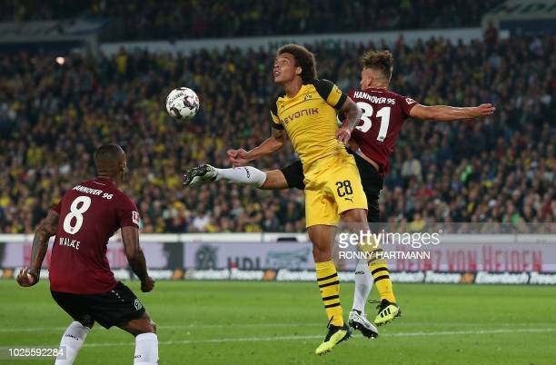 Dortmund's Belgian midfielder Axel Witsel and Hanover's German defender Waldemar Anton head for the ball during the German first division Bundesliga...