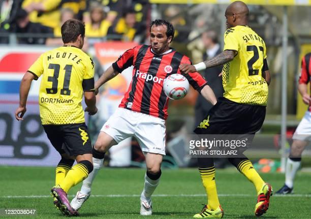 Dortmund's Brazilian defender Felipe Santana and Dortmund's midfielder Mario Goetze pressure Frankfurt's Greek striker Theofanis Gekas during the...