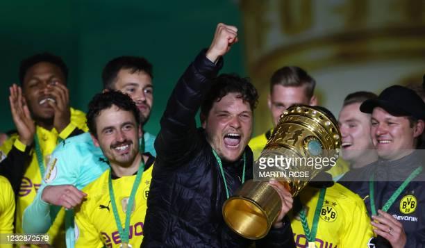 Dortmund's coach Edin Terzic holds the trophy as Dortmund's players celebrate after winning the German Cup final football match RB Leipzig v BVB...