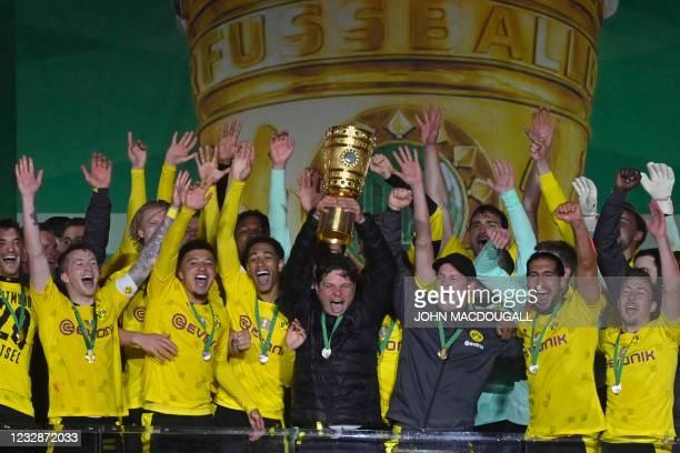 Dortmund's coach Edin Terzic lifts the trophy after the German Cup final football match RB Leipzig v BVB Borussia Dortmund, in Berlin on May 13,...
