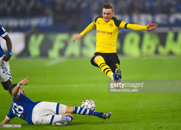 Dortmund's Danish forward Jacob Bruun Larsen and Schalke's German midfielder Daniel Caligiuri vie for the ball during the German first division...