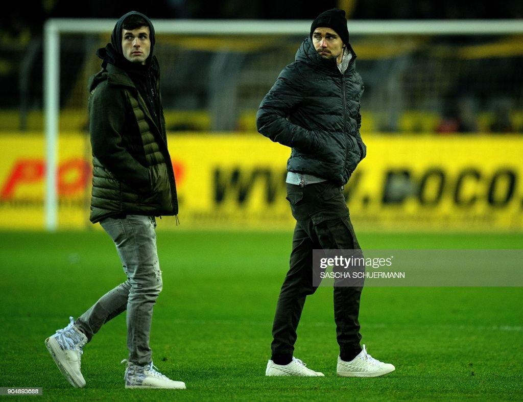 Dortmund's defender Marcel Schmelzer (R) and Dortmund's US midfielder Christian Pulisic walk on the pitch after the German first division Bundesliga football match BVB Borussia Dortmund vs VfL Wolfsburg, in Dortmund, western Germany, on January 14, 2018. /