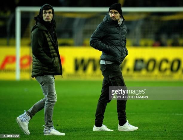 Dortmund's defender Marcel Schmelzer and Dortmund's US midfielder Christian Pulisic walk on the pitch after the German first division Bundesliga...