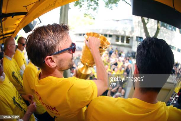 Dortmund's defender Marcel Schmelzer hold the trophy as players arrive at Borsigplatz during celebrations after winning the German Cup final in...