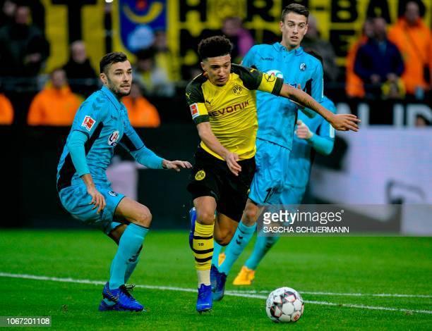 Dortmund's English midfielder Jadon Sancho and Freiburg's German defender Manuel Gulde vie for the ball during the German first division Bundesliga...