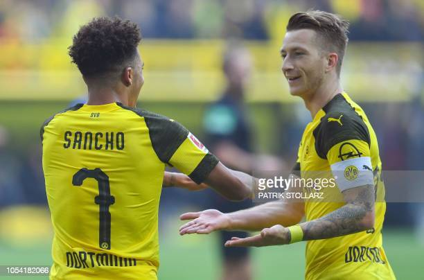 Dortmund's English midfielder Jadon Sancho celebrates scoring the opening goal with Dortmund's German forward Marco Reus during the German first...