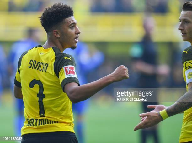 Dortmund's English midfielder Jadon Sancho celebrates scoring the opening goal with Dortmund's German forward Marco Reus during the German first...