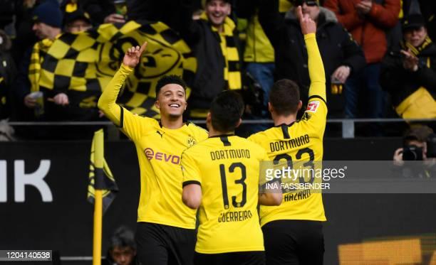 Dortmund's English midfielder Jadon Sancho Dortmund's Portuguese defender Raphael Guerreiro and Dortmund's Belgian forward Thorgan Hazard celebrate a...