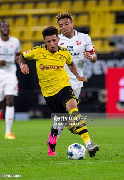 Dortmund's English midfielder Jadon Sancho is chased by Mainz' Cameroonian midfielder Kunde Malong during the German first division Bundesliga...