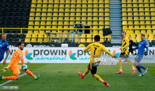 Dortmund's English midfielder Jadon Sancho scores against Hoffenheim's German goalkeeper Oliver Baumann during the German first division Bundesliga...