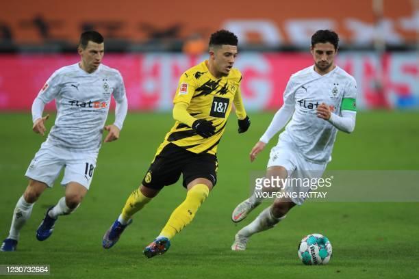 Dortmund's English midfielder Jadon Sancho vies for the ball with Moenchengladbach's Austrian defender Stefan Lainer and Moenchengladbach's German...