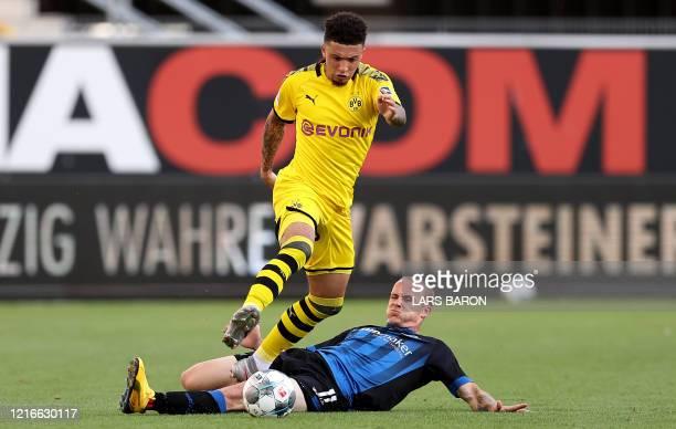 Dortmund's English midfielder Jadon Sancho vies with Paderborn's German forward Sven Michel during the German first division Bundesliga football...