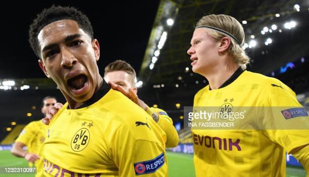 Dortmund's English midfielder Jude Bellingham celebrates scoring the opening goal with his teammates including Dortmund's Norwegian forward Erling...