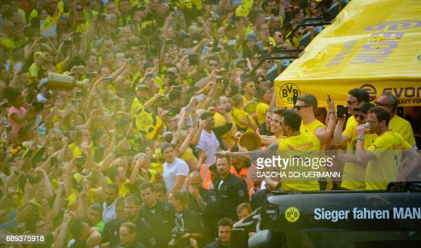 Dortmund's fans celebrate as the players arrive at Borsigplatz during celebrations after winning the German Cup final in Dortmund western Germany on...