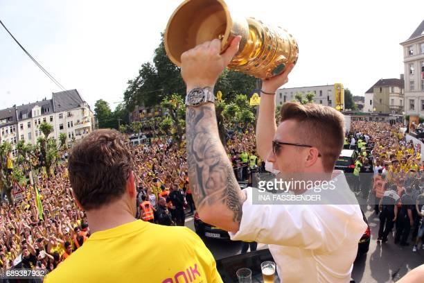 Dortmund's forward Marco Reus celebrates with the trophy as they arrive at Borsigplatz during celebrations after winning the German Cup final in...