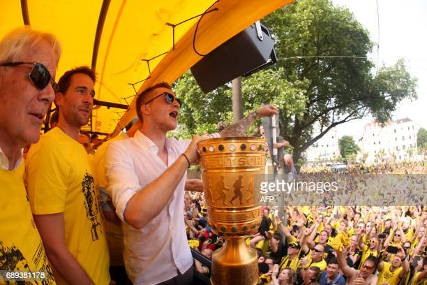 Dortmund's forward Marco Reus hold the trophy as players arrive at Borsigplatz during celebrations after winning the German Cup final in Dortmund...