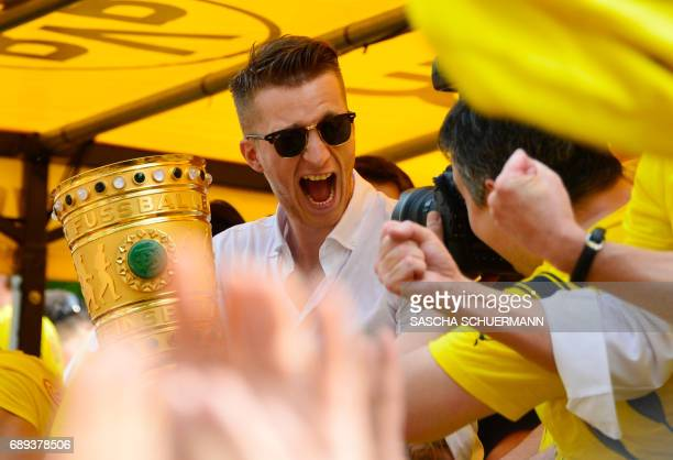 Dortmund's forward Marco Reus holds the trophy as Borussia Dortmund players arrive at Borsigplatz during celebrations after winning the German Cup...