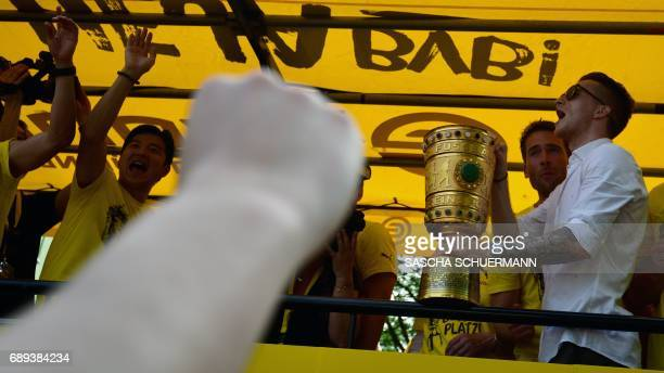 Dortmund's forward Marco Reus holds the trophy as he and his teamates arrive at Borsigplatz during celebrations after winning the German Cup final in...