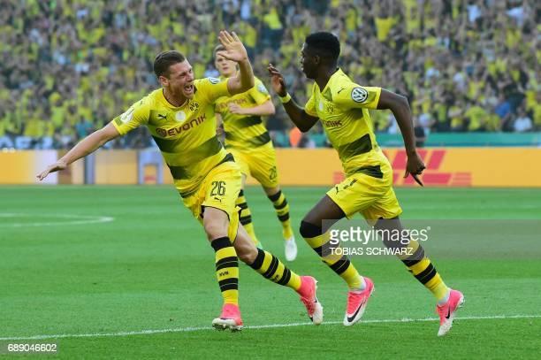 Dortmund's French midfielder Ousmane Dembele celebrates scoring the opening goal with his teammate Polish defender Lukasz Piszczek during the German...
