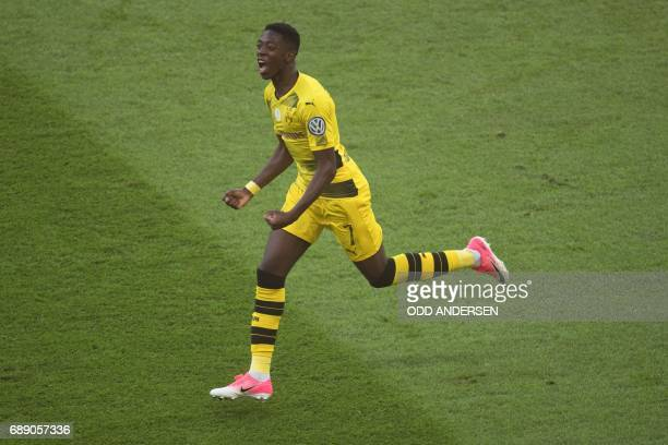 Dortmund's French midfielder Ousmane Dembele celebrates scoring the opening goal with Polish defender Lukasz Piszczek during the German Cup final...