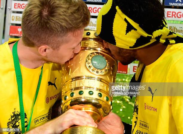 Dortmund's Gabonese forward PierreEmerick Aubameyang and Dortmund's forward Marco Reus kiss the trophy after victory during the German Cup final...