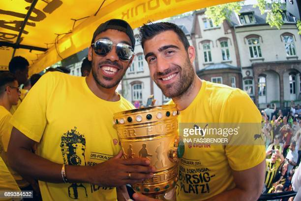 Dortmund's Gabonese forward PierreEmerick Aubameyang and Dortmund's Greek defender Sokratis pose with the trophy as they arrive at Borsigplatz during...