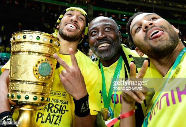 Dortmund's Gabonese forward PierreEmerick Aubameyang and his father Pierre Francois Aubameyang and brother Willy Aubameyang celebrate with the trophy...